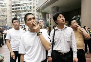 Chinos contemplando noticias en las pantallas LED de la calle, mientras fuman